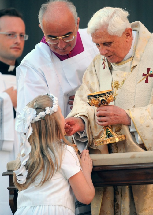 GIRL KNEELS AS SHE RECEIVES COMMUNION FROM POPE